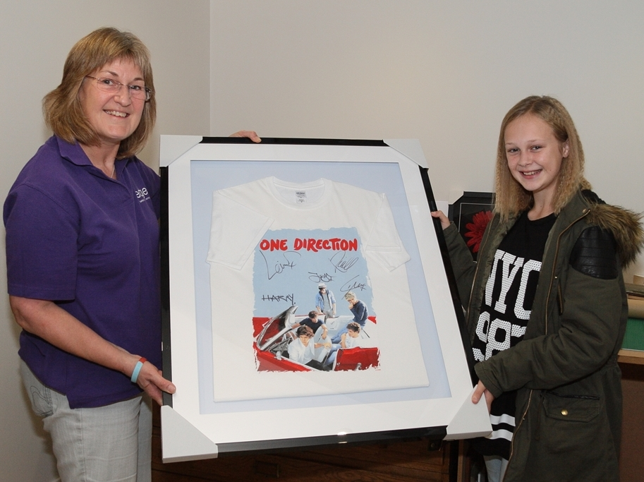 Bev presents Paige with her framed One Direction T-shirt